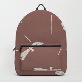 White Dragonflies against dark brown background.  Backpack