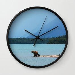 A MOTHER BEAR TEACHES HER CUBS TO SWIM ON THE EDGE OF NAKNEK LAKE IN ALASKA'S KATMAI NATIONAL PARK Wall Clock