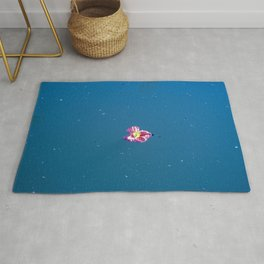 A pink blossom floating in a contrast blue lake Rug