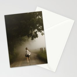woman running down a lane in the country morning fog Stationery Cards