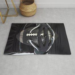 Black gloved hands holding a black American Football Rug