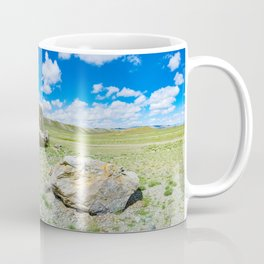 Tarkhatinsky megalithic complex. Steppe and blue mountains on the horizon. Altai Russia. Coffee Mug