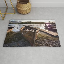 Wooden rowing boats on shore of Lake Derwentwater, England Rug