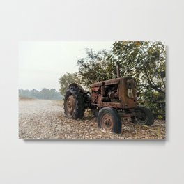 Old tractor on a pebble beach by a river Metal Print