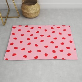 Little red hearts scattered on pink background Rug
