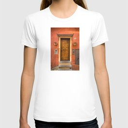 Wooden door of Tuscany with typical bright colors on its walls. Next to two small pots with flowers T-shirt